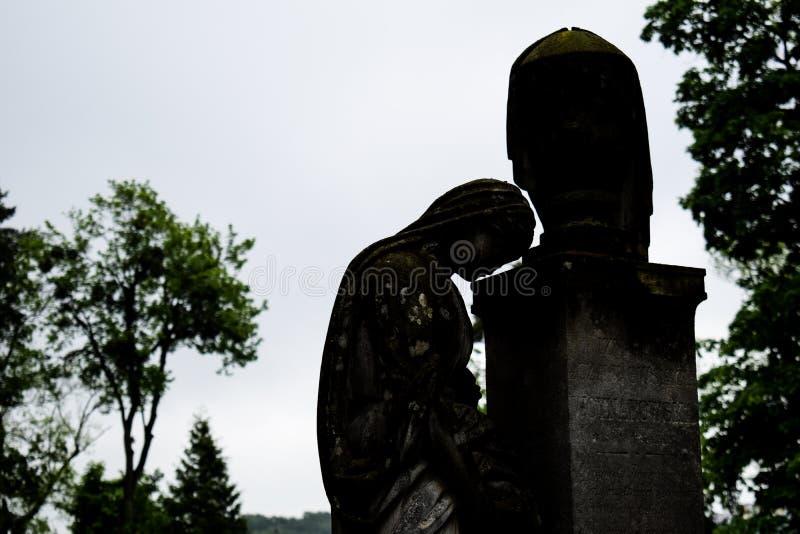 老墓碑纪念雕象在古老公墓 女孩美丽的哀伤的雕象在利沃夫州老公墓  免版税库存照片