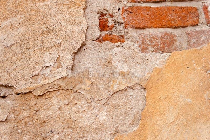 老墙壁背景概略的土气破旧的纹理有黄色破裂的膏药和葡萄酒红砖的 免版税库存图片