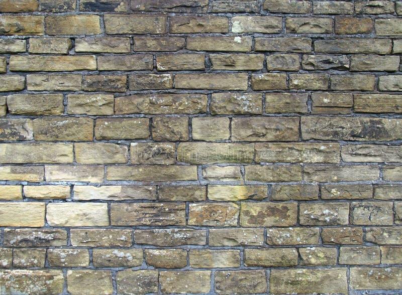 老外墙由粗砺的黄褐色沙粒石头做成块  免版税库存照片