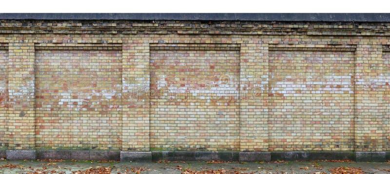 老多斑点的黄色砖变老了被隔绝的篱芭长的片段  库存照片