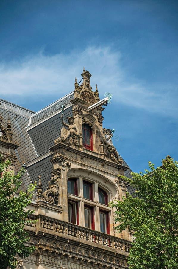 老大厦门面和屋顶装饰特写镜头,与树和晴朗的蓝天在阿姆斯特丹 库存照片