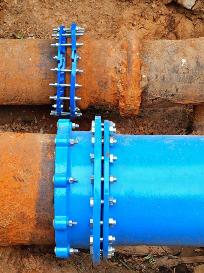 老大饮料水管加入与新的蓝色阀门和新的蓝色联合成员 完成的被修理的管道系统等待的覆盖物  免版税库存图片