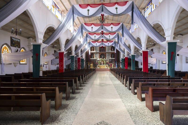 老天主教和宗教标志内部与祷告摊的在湖Atitlan岸的圣胡安村庄在Guatemal 免版税库存照片