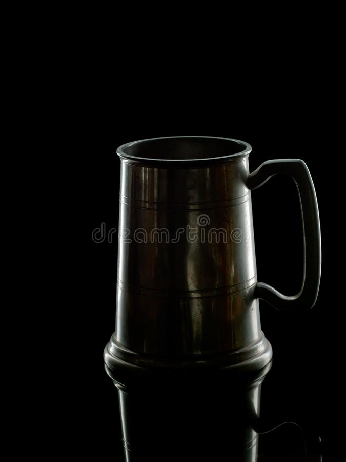 老奖杯饮用的杯子,大啤酒杯 后面照明设备 库存照片