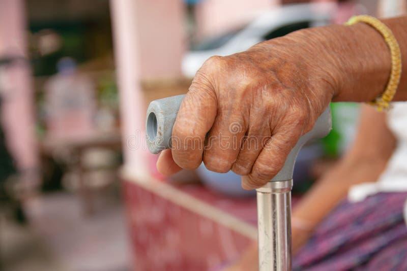 老妇人亚洲的手用藤茎拐棍 免版税库存照片