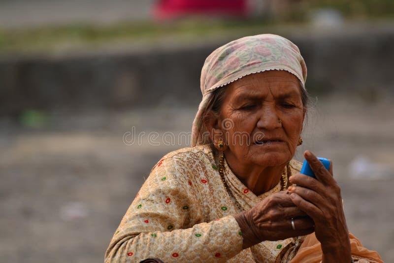 老妇人使用手机用两手 免版税库存图片