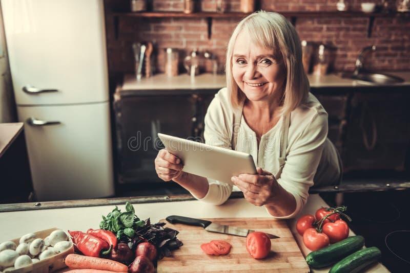 老妇人在厨房里 免版税图库摄影