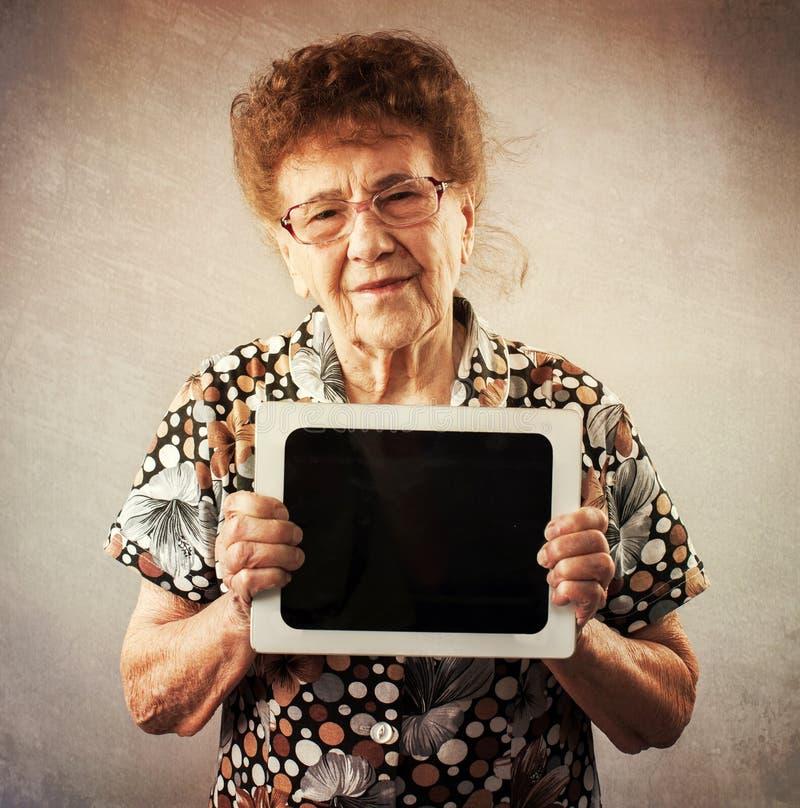 老妇人在手上的拿着一种片剂  库存图片