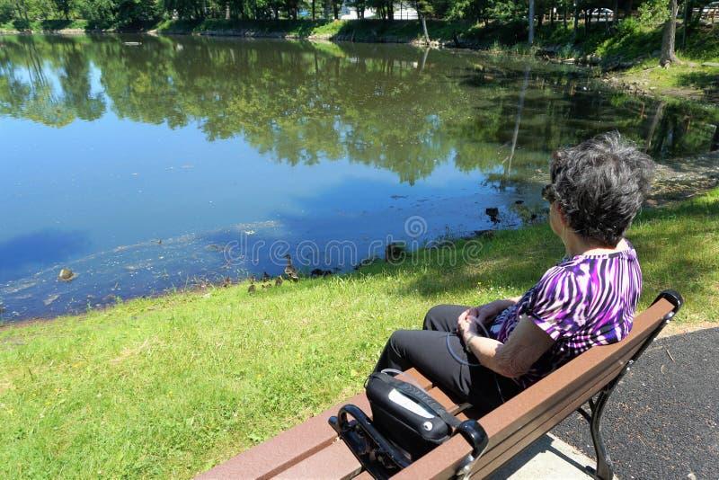 老妇人坐与看池塘的氧气罐的长凳 图库摄影