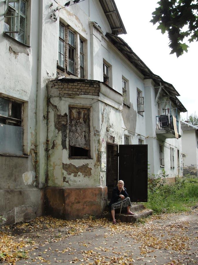 老妇人坐被破坏的房子门廊在贫民区 免版税库存照片