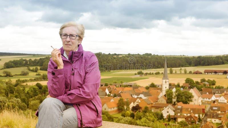 老妇人坐长凳和抽烟 免版税库存图片