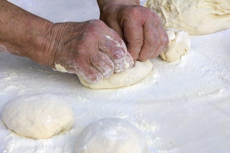 老妇人手揉面团 免版税图库摄影