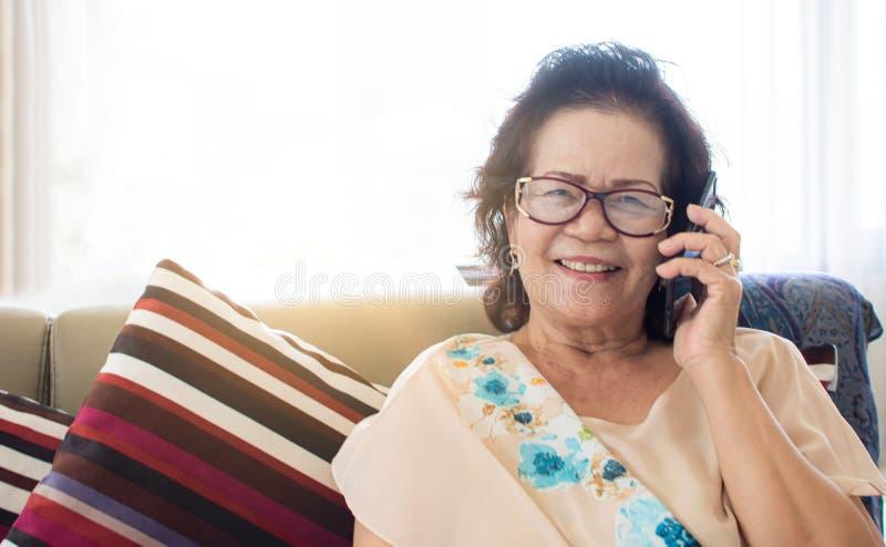 老妇人是愉快的为在家使用手机 免版税图库摄影