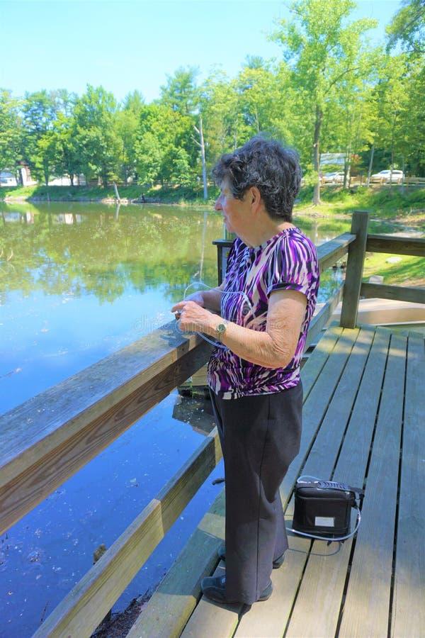 老妇人景色筑成池塘与便携式的氧气管 库存照片