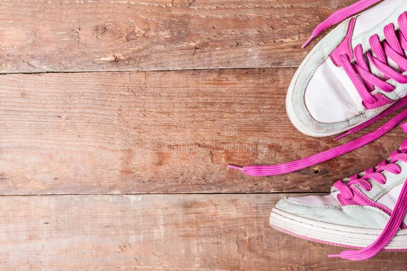 老妇人有桃红色鞋带的` s运动鞋在老委员会 如何选择新的运动鞋?复制文本的空间 免版税库存照片