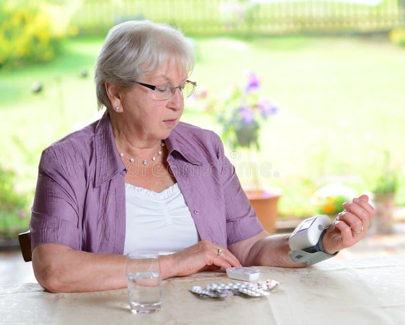 老妇人测量血压 免版税库存照片