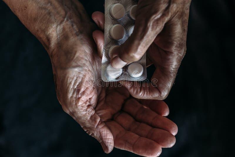 老妇人的手有片剂或药片的 老人的医疗保健和采取疗程 库存图片