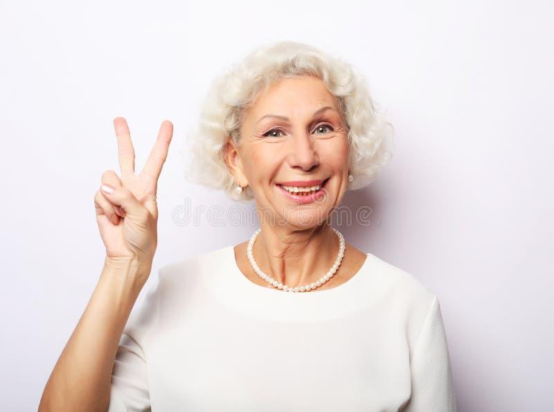 老妇人笑和显示和平或胜利signat照相机 情感和感觉 传神祖母画象  图库摄影