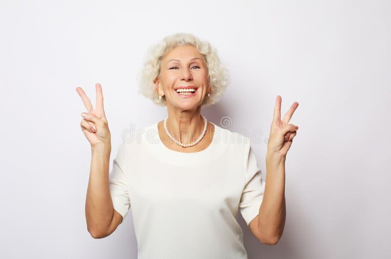 老妇人笑和显示和平或胜利signat照相机 情感和感觉 传神祖母画象  库存图片