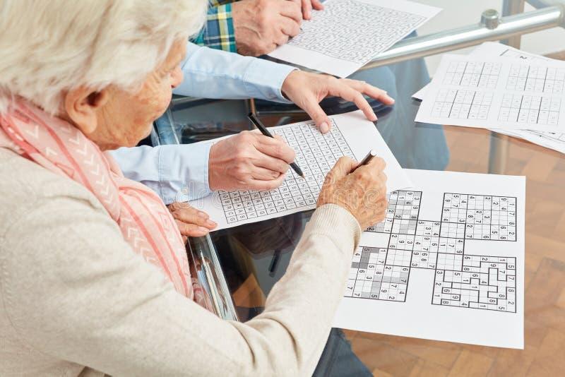 老妇人解决sudoku难题当记忆训练 库存照片