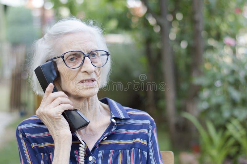 老妇人谈话在电话在后院 免版税图库摄影
