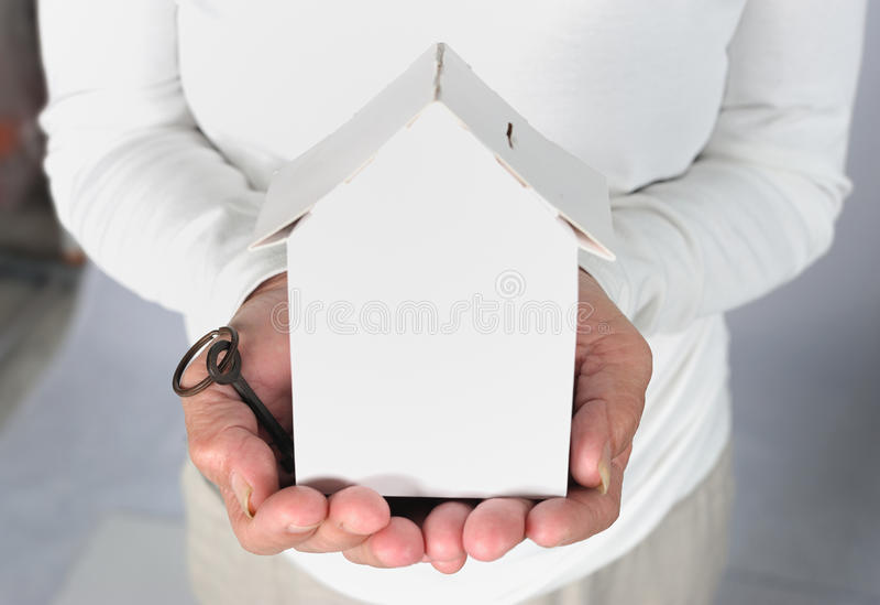 老妇人递把握房子模型和关键 免版税库存图片