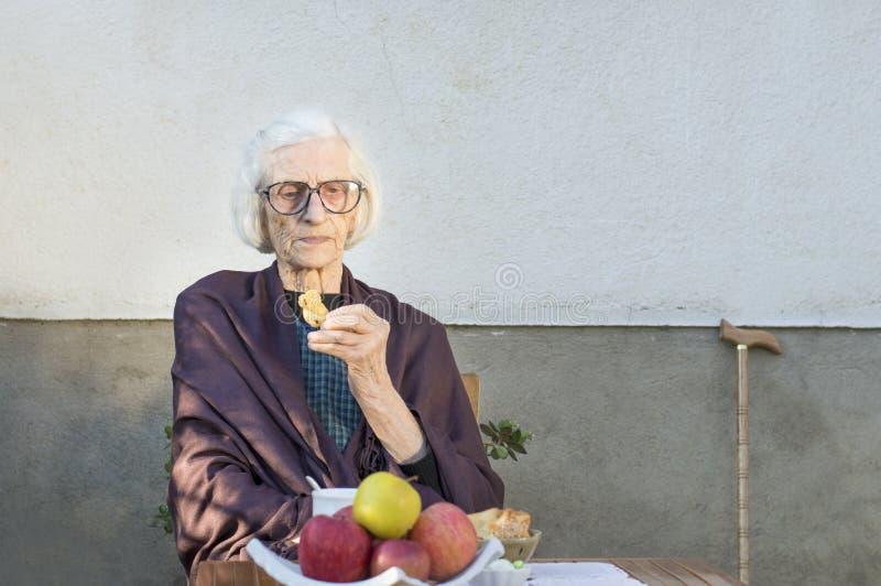 老妇人食用快餐在后院 免版税库存照片