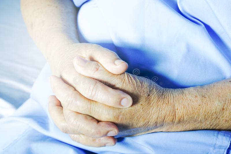 老妇人`手在医院的床上 免版税库存图片