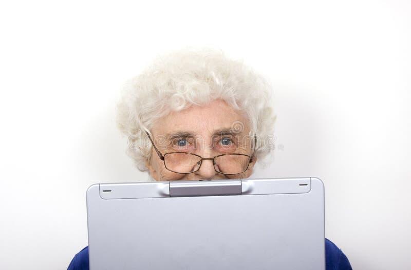 老婆婆她的膝上型计算机 免版税库存图片