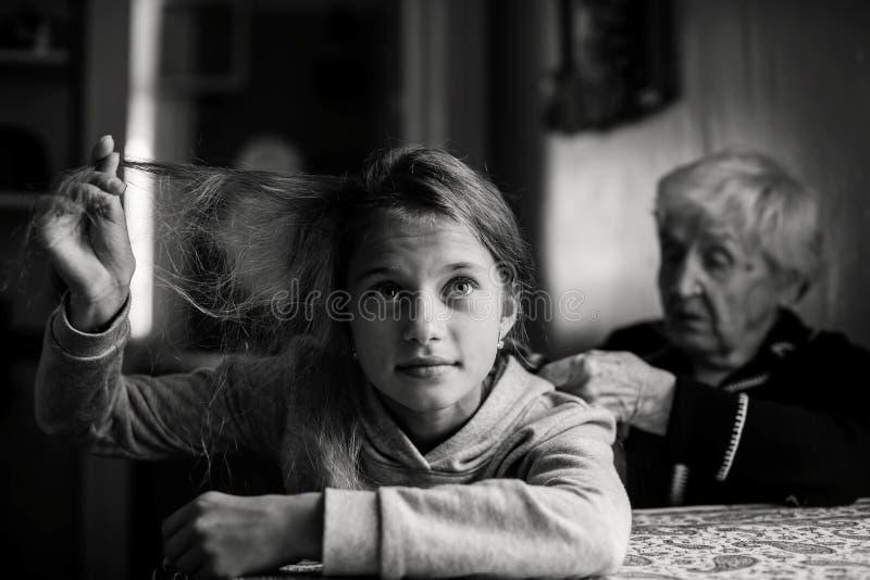老婆婆,老妇人把她的重孙女的头发编成辫子 免版税库存图片