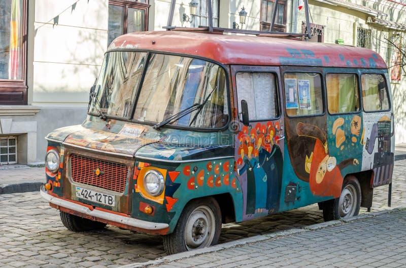 老嬉皮的样式的葡萄酒减速火箭的被抛弃的汽车被绘的街道画艺术家是残破的在其中一条利沃夫州街道  免版税图库摄影