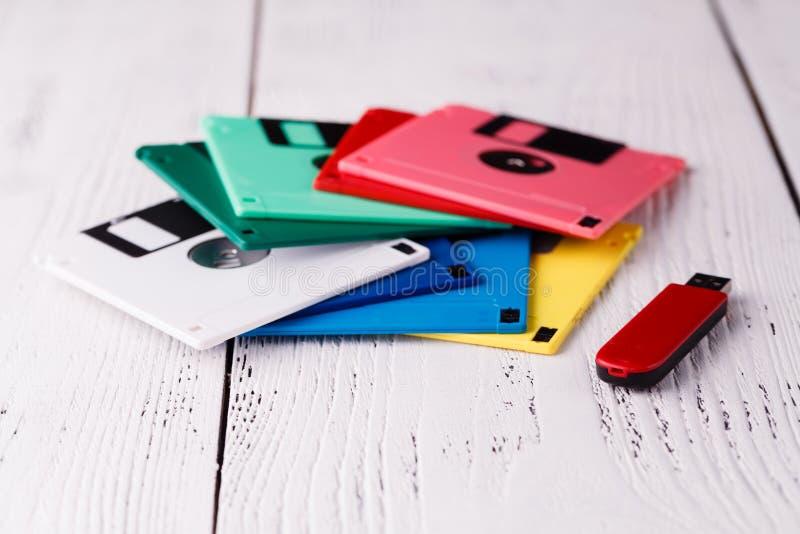 老存贮软盘在木桌上对USB磁盘司机 免版税库存照片