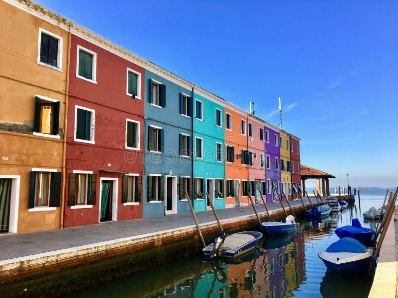 老家五颜六色的行沿运河和在海旁边,在一个安静的晴朗的早晨在Burano美丽的镇,意大利 免版税图库摄影