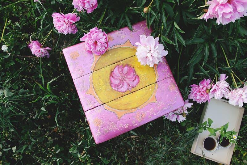 老家具恢复 手工制造老板凳绘与丙烯酸漆在夏天庭院里在有开花的乡下 库存照片