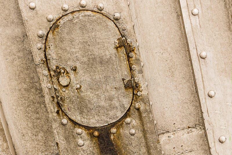 老小生锈的舱口盖卵形门老小船风化了灰色金属有锁铆钉工业特写镜头的背景 库存照片