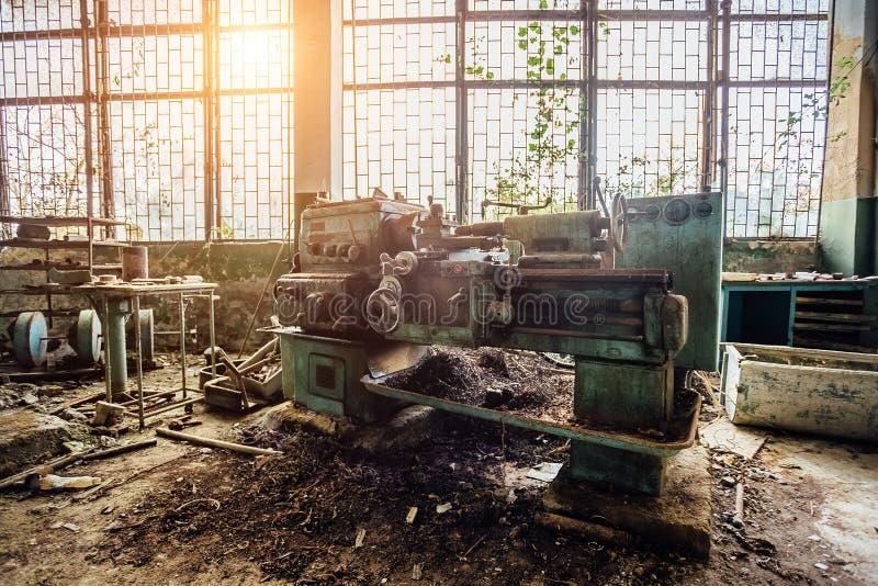 老工业机械工具 生锈的金属设备在被放弃的长满的工厂 免版税库存图片
