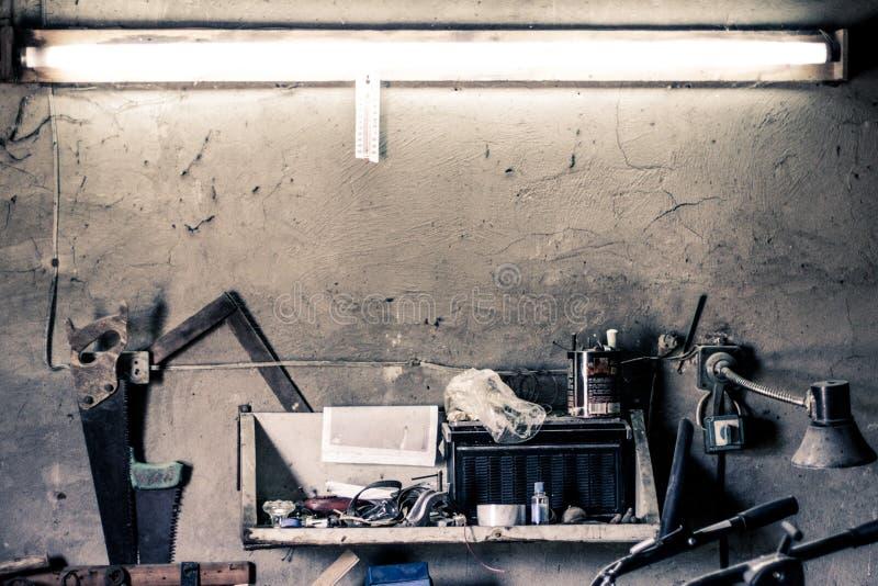 老工作工具,在墙壁上的架子在一个家庭车库的一个老葡萄酒工作凳 库存照片
