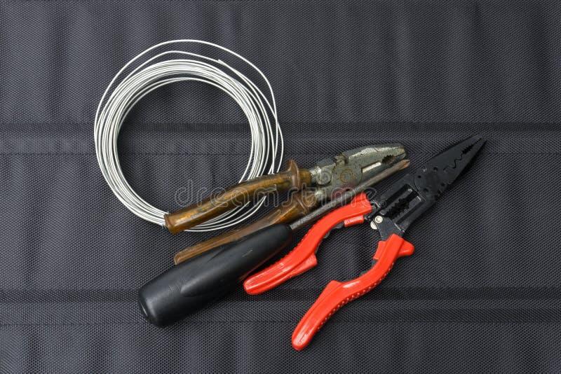 老工具、钳子、螺丝刀和导线 免版税库存照片