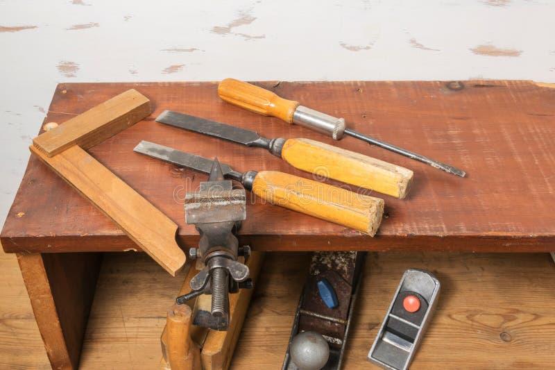 老工具 凿子、螺丝刀和正方形在架子 在一张木桌上的整平机 免版税库存照片