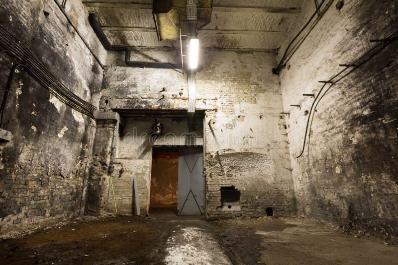 老工厂厂房,与一点光的地下室 免版税库存图片