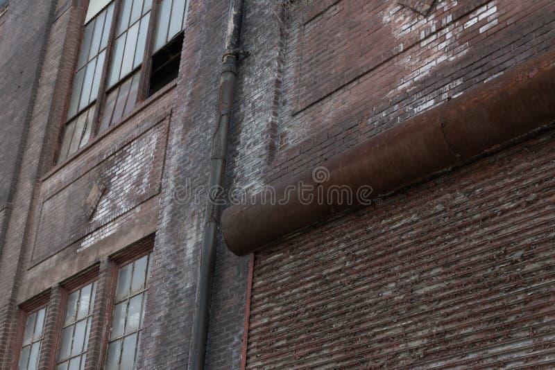 老工厂厂房,与卷起门的生锈的砖块建筑细节  库存照片