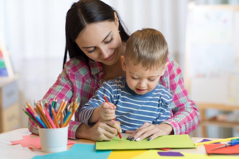 老师与儿童男孩的妇女图画在教室 库存图片