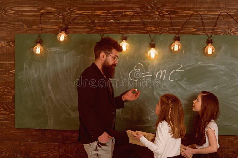 老师和女孩学生在黑板附近的教室 有胡子的人在正式衣服教女小学生物理 库存照片