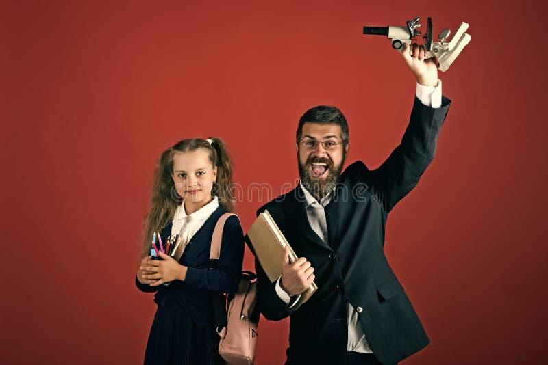 老师和女小学生有愉快的面孔的在赤土陶器背景 免版税图库摄影