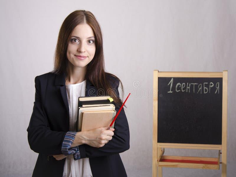 老师和委员会的画象有课本的在背景中 免版税图库摄影