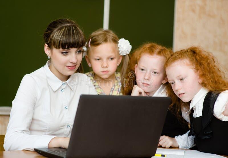 老师和学生在教室使用计算机 免版税图库摄影