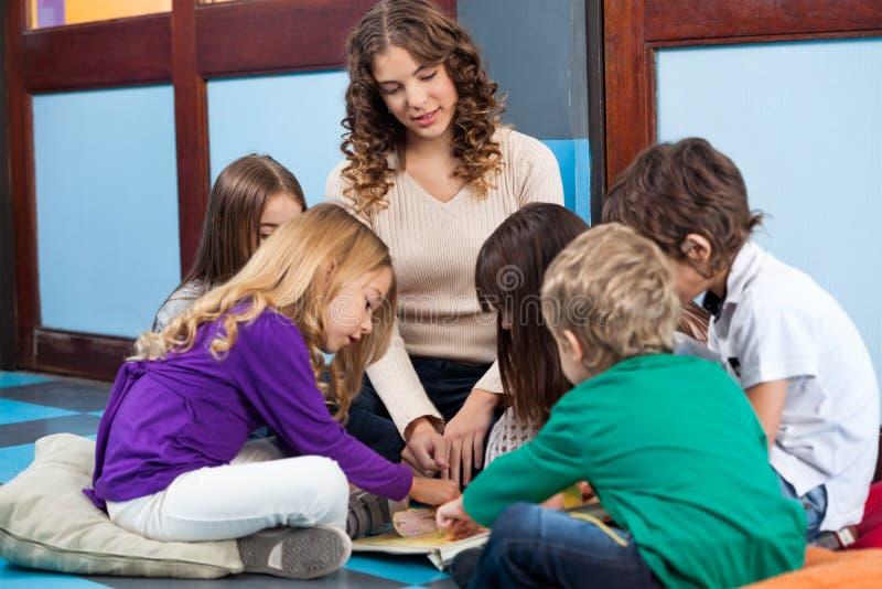 老师和学生阅读书在幼儿园 图库摄影
