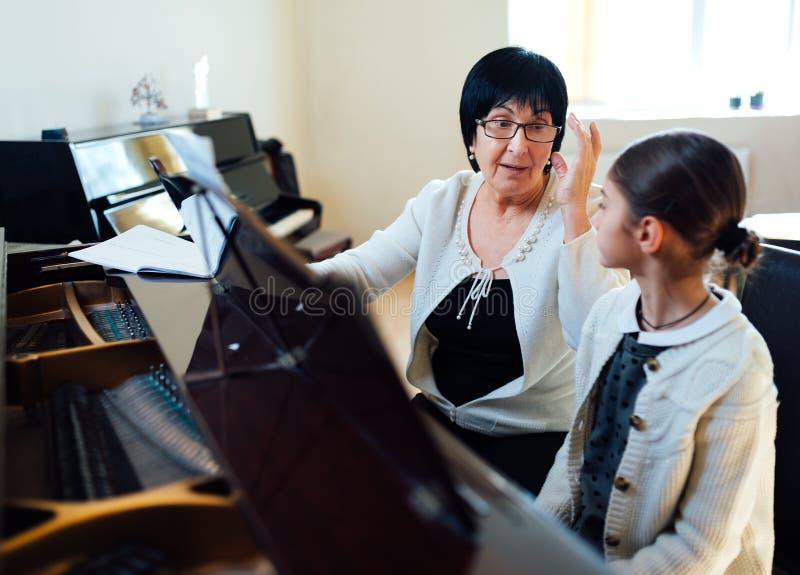 老师和学生类钢琴的 免版税库存照片