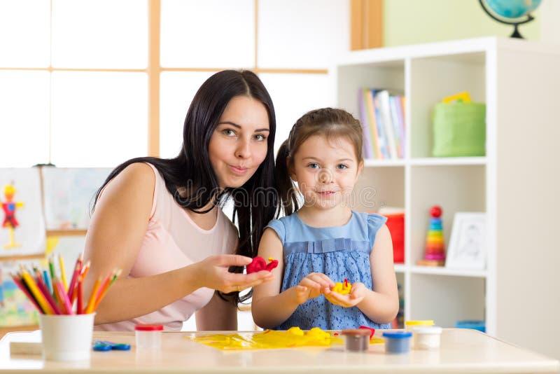 老师和小女孩孩子在幼儿园学会从彩色塑泥的模子 免版税库存照片