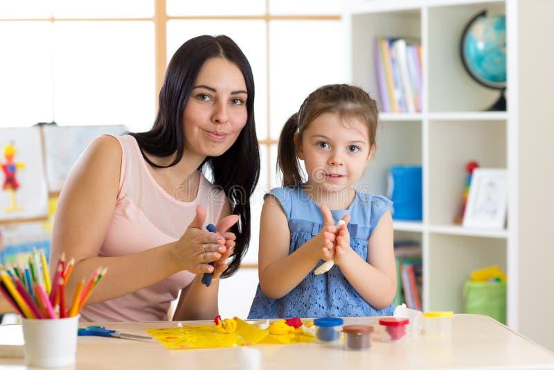 老师和小女孩孩子学会从彩色塑泥的模子在托儿所 免版税库存图片